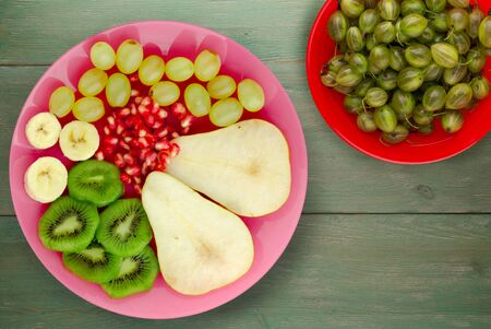 fruit mix pear, kiwi, grapes, banana, pomegranate on a green wooden background. fruit on a pink plate top view