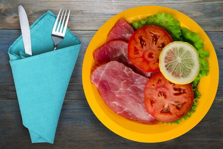 ham with salad, tomato and lemon on a yellow plate. ham on a blue wooden background .ham with fork and knife top view