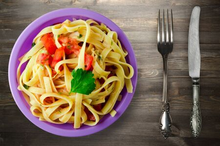 spaghetti on purple plate with fork and knife top view. spaghetti tomatoes, onions, cabbage on black wooden background