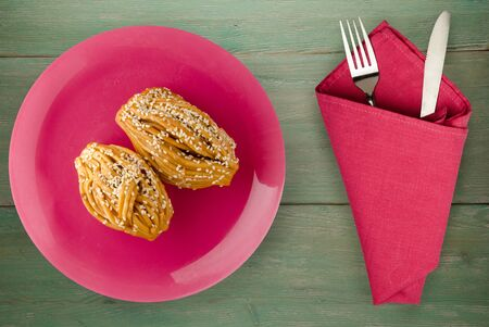 cakes with sesame seeds on a pink plate with fork and knife top view. cakes with sesame seeds on a green wooden background