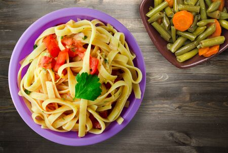 spaghetti on purple plate with vegetarian salad top view. spaghetti tomatoes, onions, cabbage on black  wooden background