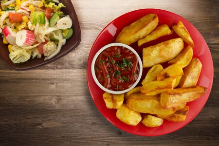 french fries with ketchup on brown wooden background. french fries on red plate with vegetable salad top view