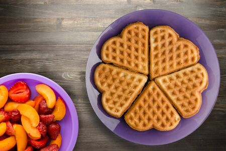 Belgian waffles with fruits on a black wooden background. waffles on a purple plate top view 版權商用圖片