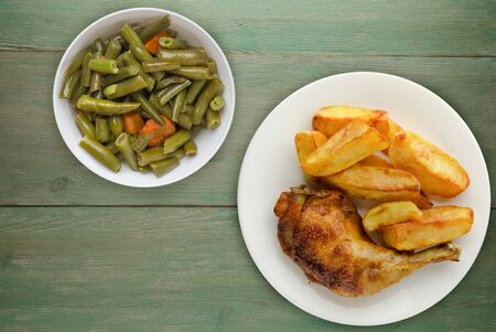 Chicken thigh with french fries on a green wooden background. chicken thigh on a white plate with vegetable salad . rustic food 版權商用圖片 - 148096396