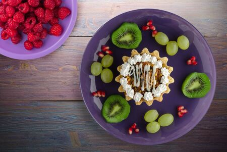 dessert of cake and fruit grapes, kiwi, pomegranate on a purple wooden background. dessert on a purple plate top view