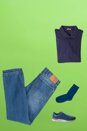 flat lay, men's fashion.blue jeans ,blue sneakers,dark bue t-shirt,dark blue socks on lime background. casual clothes top view