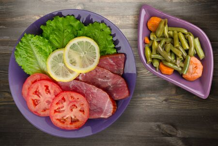 ham with salad, tomato and lemon on a purple plate. ham on a black wooden background .ham with vegetable salad top view