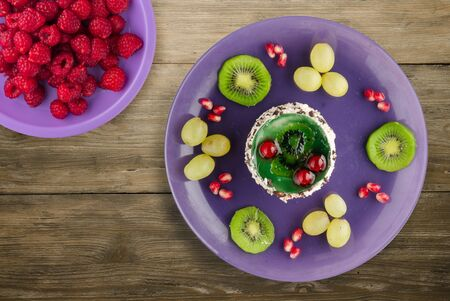 dessert of cake and fruit grapes, kiwi, pomegranate on a wooden background. dessert on a purple plate with fruits top view