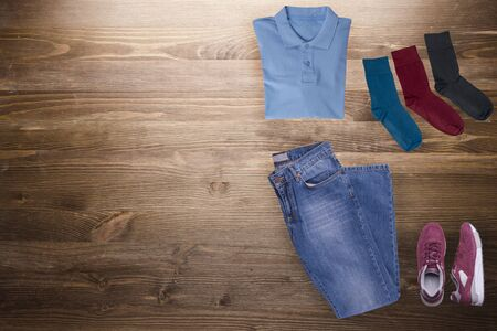 flat lay, men's fashion.blue jeans,red sneakers,blue t-shirt,multi-colored socks on a wooden background. casual clothes top view