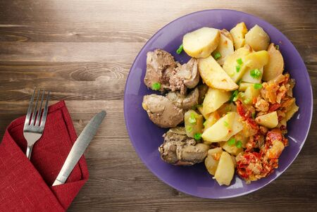 fried liver with potatoes and stewed tomatoes with fork and knife top view. fried liver on plate on a wooden background