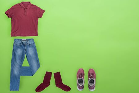 flat lay, men's fashion.blue jeans ,blue sneakers,dark red t-shirt,different colors socks on lime background. casual clothes top view