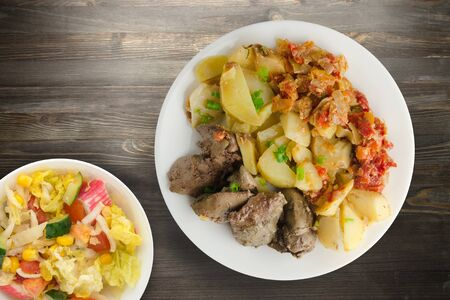 fried liver with potatoes and stewed tomatoes with vegetable salad. fried liver on white plate on black wooden background top view