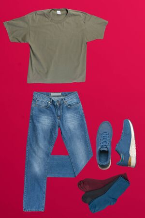 flat lay, men's fashion.blue jeans ,blue sneakers,olive t-shirt,different colors socks on red background. casual clothes top view
