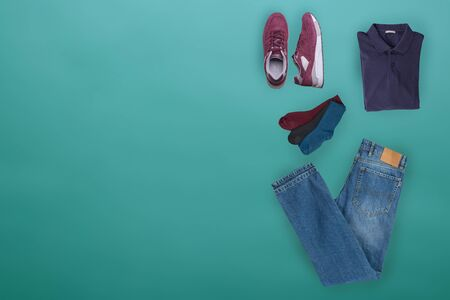 flat lay, men's fashion.blue jeans ,red sneakers,dark blue t-shirt,different colors socks on turquoise background. casual clothes top view