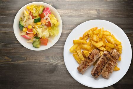 pork ribs and potatoes on a white plate with vegetable salad and sauce on a black wooden background. Top view of fast food. unhealthy food.flat lay
