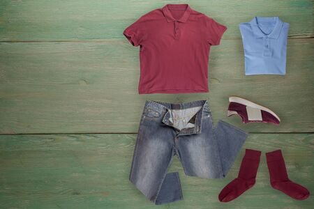 flat lay, men's fashion.grey jeans ,red sneakers,burgundy t-shirt,dark red socks on a wooden background. casual clothes top view 版權商用圖片