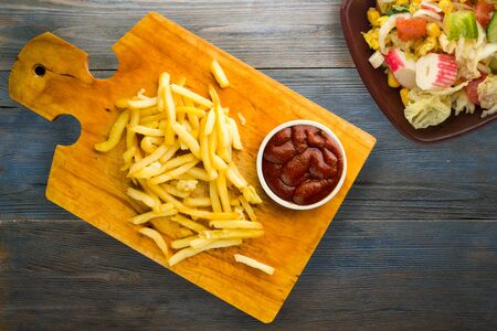 french fries with ketchup on grey blue wooden background. french fries on brown wooden plate with vegetarian salad top view
