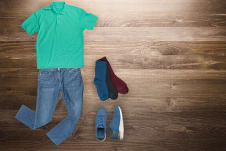 flat lay, men's fashion.blue jeans ,blue sneakers,green t-shirt,several color socks on a wooden background. casual clothes top view