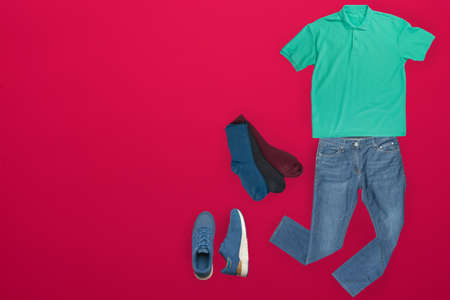 flat lay, men's fashion.blue jeans ,blue sneakers,green t-shirt,different clors socks on red background. casual clothes top view