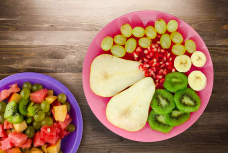fruit mix pear, kiwi, grapes, banana, pomegranate on a brown wooden background. fruit on a pink plate top view