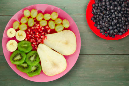 fruit mix pear, kiwi, grapes, banana, pomegranate on a green wooden background. fruit on a pink plate Banque d'images