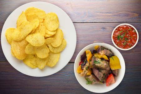 potato chips on a white plate with vegetarion salad. chips on a purple wooden background top view. 写真素材