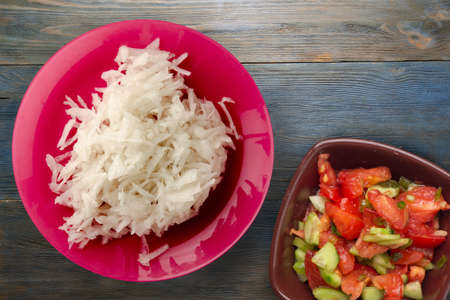 daikon on blue gray wooden background. daikon on red plate with vegetarian salad top view 免版税图像