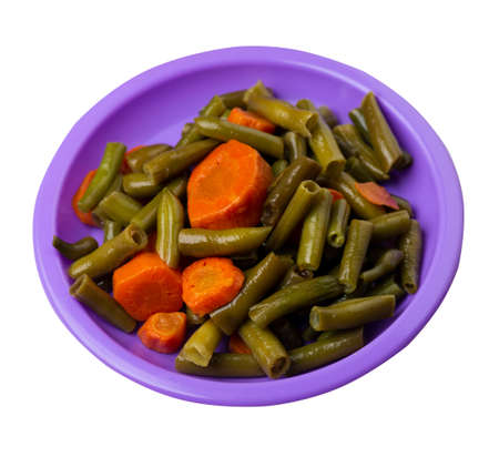 green beans with garlicand carrots on purple plate isolated on white background.green beans with carrot top view. healthy vegetarian food 免版税图像