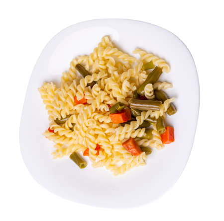 pasta with green beans with garlicand carrots on white plate isolated on a white background. Mediterranean Kitchen. pasta with vegetables top view. 免版税图像