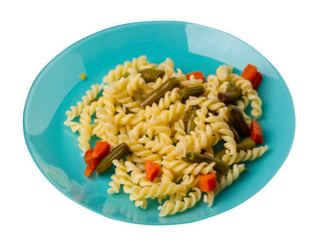 pasta with green beans with garlicand carrots on turquoise plate isolated on a white background. Mediterranean Kitchen. pasta with vegetables top side view.
