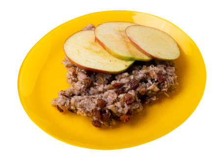 rye flakes with raisins and apples on yellow plate. rage flakes isolated on white background. healthy breakfast top side view