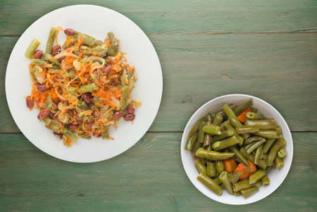 Vegetarian salad top view. Healthy food. Salad of beans, asparagus, onion, carrot and sesame on a white plate on a green wooden background.