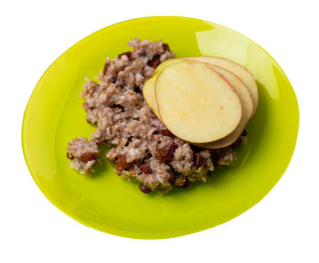 rye flakes with raisins and apples on lime plate. rage flakes isolated on white background. healthy breakfast top side view