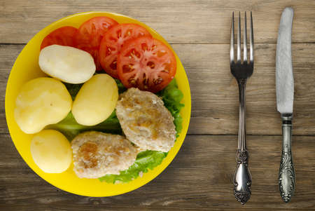 cutlet with potatoes on yellow plate with fork and knife top view. cutlet with potatoes on brown wooden background