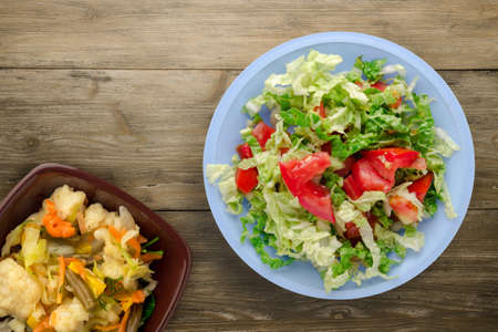 vegetarian food top view. salad of cabbage tomato on light blue plate on brown wooden background. healthy food Banco de Imagens