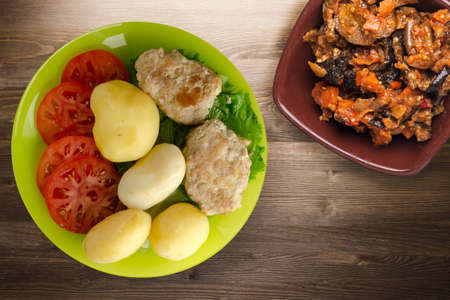 cutlet with potatoes on lime plate with vegetable salad top view. cutlet with potatoes on brown wooden background