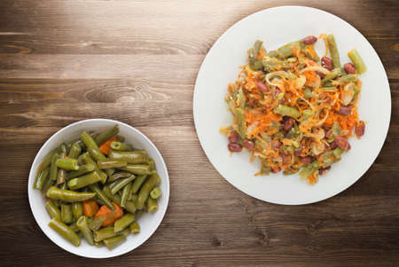 Vegetarian salad top view. Healthy food. Salad of beans, asparagus, onion, carrot and sesame on a white plate on a brown wooden background. Banque d'images