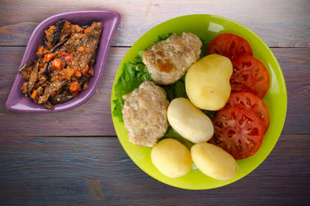 cutlet with potatoes on lime plate with vegetable salad top view. cutlet with potatoes on purple wooden background