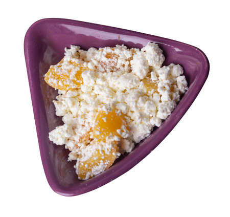 cottage cheese with peaches on red brown plate isolated on white background. cottage cheese top side view. healthy breakfast