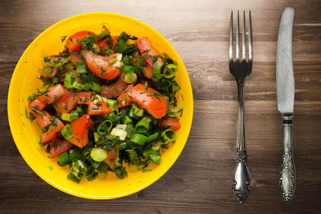 vegetarian food with knife and fork. tomatoes, onion, fennel on yellow plate on brown wooden background. healthy food top view