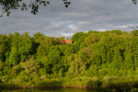 red house on the mountain covered with green trees river. Summer sunset.