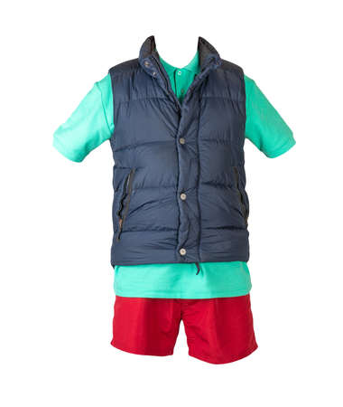 Dark blue sleeveless jacket, green t-shirt with collar on buttons and red sports shorts, isolated on white background. Current clothes for cool weather