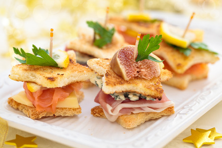 Star shaped toasts with smoked salmon,procsiutto and cheese for holidays. photo