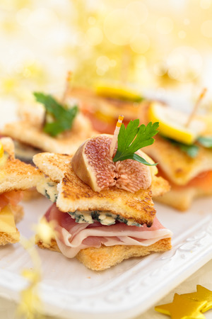 Star shaped toasts with smoked salmon,procsiutto and cheese. photo