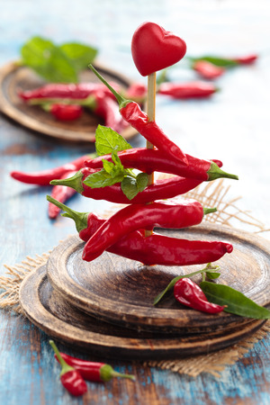 Red chili peppers with mint on sticks. photo