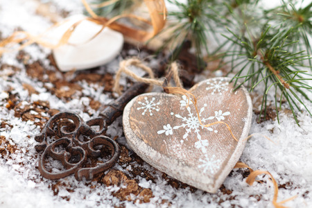Wooden heart and key on winter background. photo