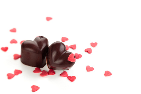 chocolate background: Homemade chocolate candies decorated with heart shaped sprinkles.