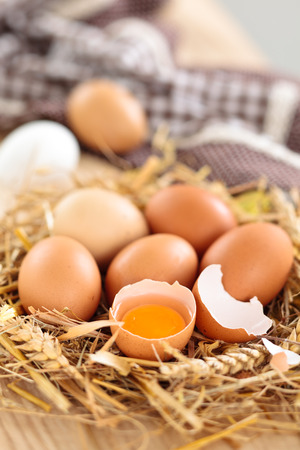 Farmers eggs in straw and tablecloth on wooden background. photo