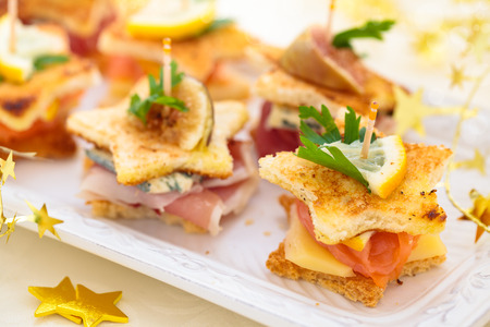 Star shaped toasts with smoked salmon, procsiutto and cheese. photo