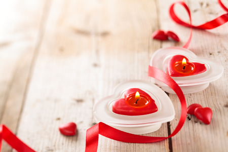 pretty s shiny: Candles, hearts and ribbon on wooden table.